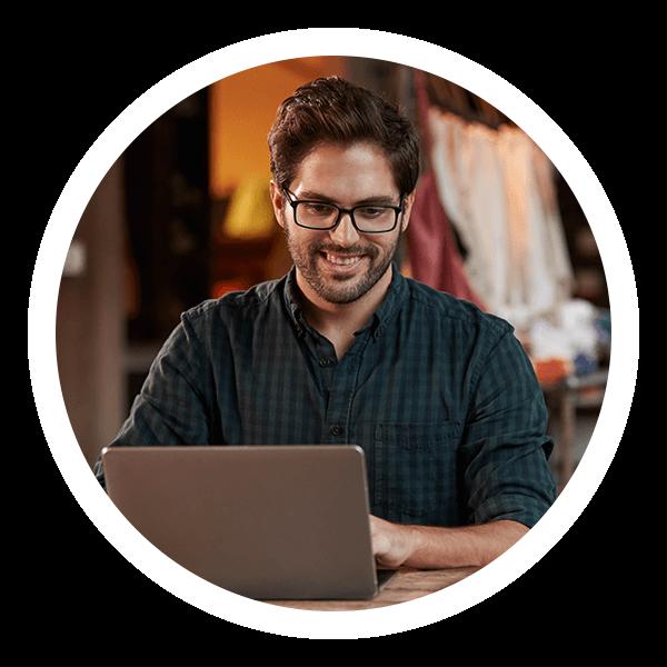 Ladenbesitzer lächelnd am Laptop